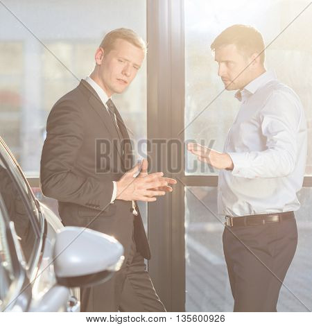 Automobile buyer discussing with a seller about car