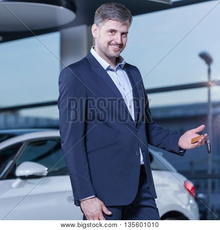 Smiling businessman buying a new luxurious car