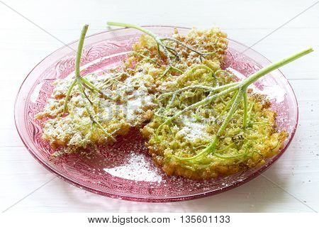 fried elderflower pancakes with powdered sugar on a pink glass dish on a white painted wooden table selected focus narrow depth of field