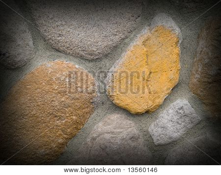 Rock And Concrete Wall With Large Rounded Stones And Dark Border