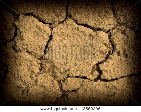 Parched And Cracked Dry Ground In Full Sunlight With Dark Edge