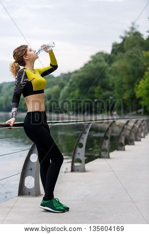 Sporty woman resting and drinking water after running outdoors