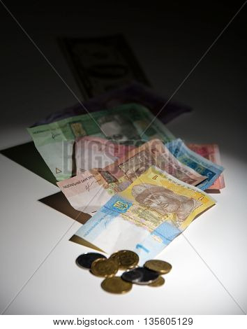 Ukrainian hryvnia and pennies on a white background with gradient to black. Hryvnia to focus on a light background is out of focus dollars on the black.