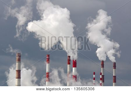 Many smoking chimneys against the gray sky