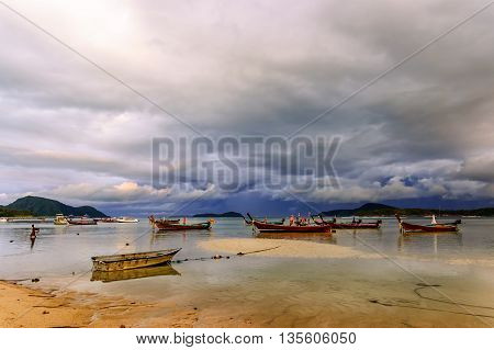 Long-tail boats stranded at low tide in evening at Rawai beach, Phuket, southern Thailand