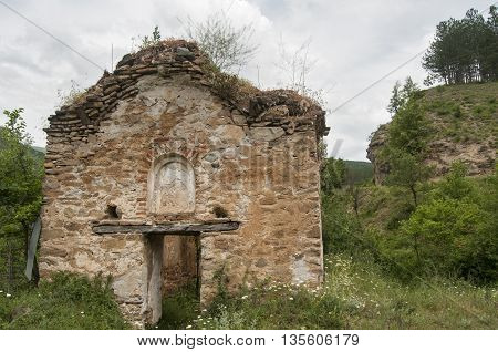 Abandoned crumbling medieval chapel exterior in mountains landscape