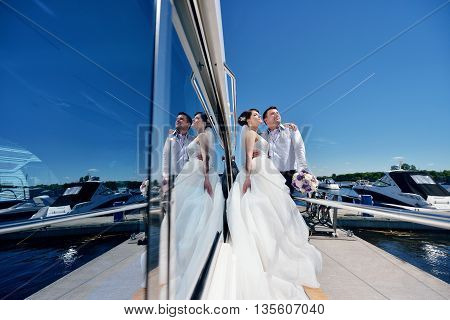 Wedding Couple Is Hugging On A Yacht. Beauty Bride With Groom. Beautiful Model Girl In White Dress.
