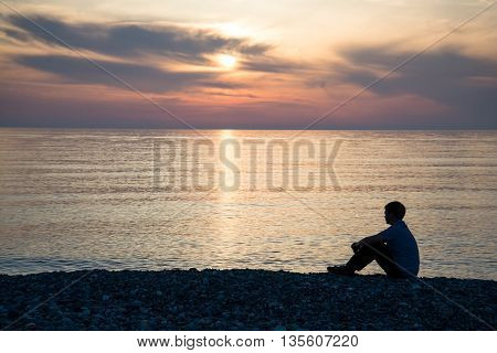 Man silhouette sitting on beach with sea and sunset background.