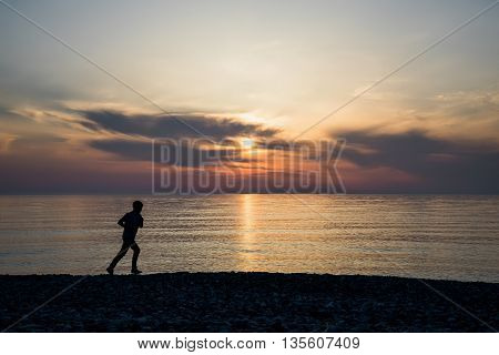 Backlight of a man running on the beach at sunset with the horizon in the background.