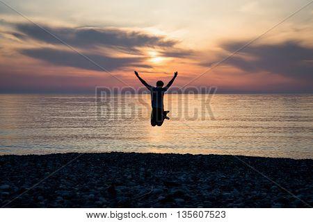 silhouette happiness man on the sunrise beach.