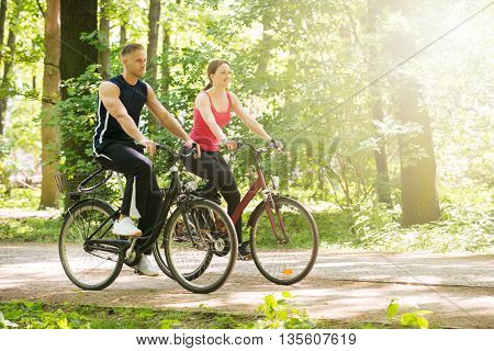 Young Happy Couple Riding Bicycles In Park