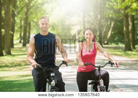 Young Happy Couple Standing With Bicycles In Park
