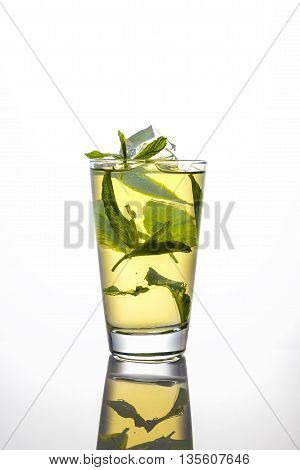 iced tea and mint in a tall glass on white background with reflection