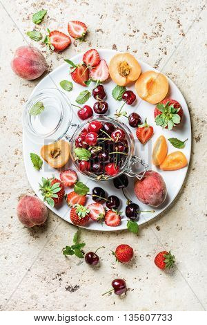 Healthy summer fruit variety. Sweet cherries, strawberries, peaches, apricots and mint leaves on white ceramic serving plate over light concrete background. Top view, selective focus