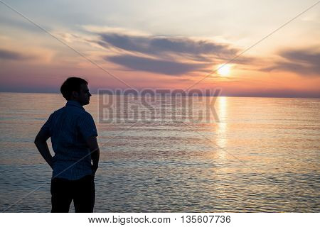Young man standing at the beach in front of amazing sea view at sunset or sunrise and thinking about his future. Rear view.