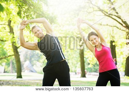 Photo Of Young Couple Exercising Together In Park