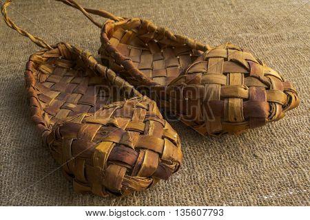souvenir vintage Russian bast shoes amid Brown burlap