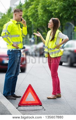 Young Couple Calling For Service On Mobile Phone With Broken Down Car On Street