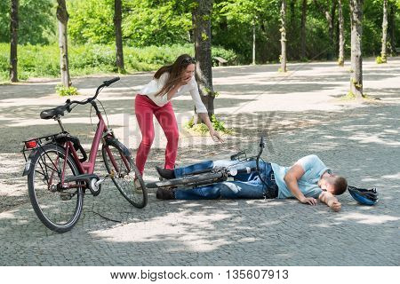 Woman Getting Worried Over Man Falling Down While Riding Bicycle