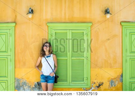 Young blond woman in typical Greek town with colorful buildings on Kastelorizo Island, Greece, Europe