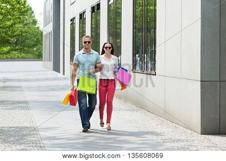 Couple Standing On Footpath Holding Multi-colored Shopping Bags