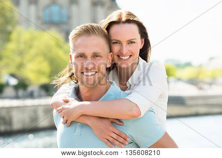 Portrait Of Young Happy Man Carrying Woman On His Back