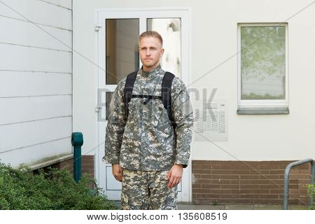 Young Male Soldier Standing Outside His House
