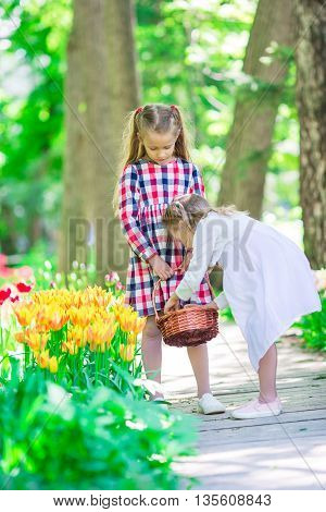 Little beautiful girls in lush tulips garden at warm spring day