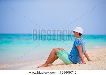 Young beautiful man listening to music on white beach
