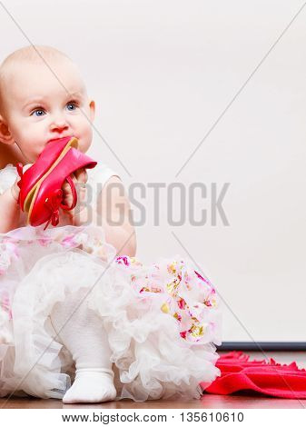 Lovely little child girl in princess fairy dress. Portrait of cute beauty sweet baby ballerina playing wit red shoes.