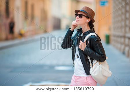 Young caucasian woman enjoy music at european city
