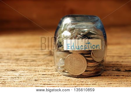 coins in glass with text educationmoney save for childen concept