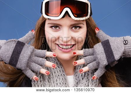 Woman skier girl wearing warm clothing ski googles portrait. Winter sport activity. Beautiful sportswoman showing gloves and red nails manicure on blue studio shot