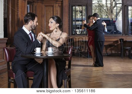 Couple Holding Hands While Man And Woman Performing Tango