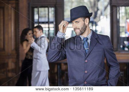 Portrait Of Tango Dancer Holding Hat In Restaurant