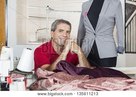 Confident Fashion Designer Sitting At Workbench