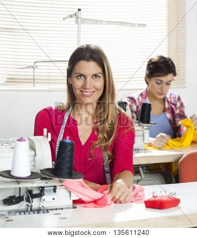 Confident Female Tailor Sitting At Workbench