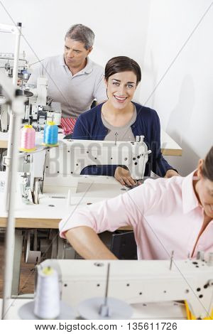 Portrait Of Happy Tailor With Colleagues Working In Factory