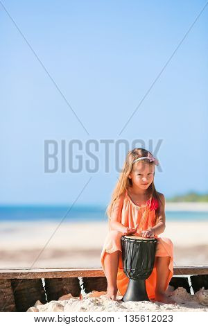 Happy toddler girl have a fun in beach cafe in exotic coastline background