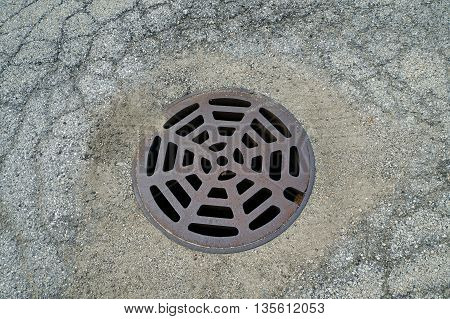 A round storm drain allows storm water to drain away from a parking lot in Naperville, Illinois.