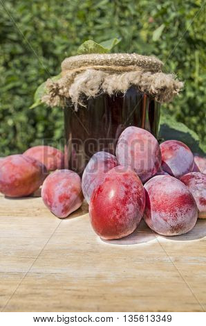 Plums jam on old wooden table. Plum jam and fresh plums over wood background