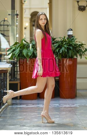 Portrait full length of young beautiful woman in red dress, shop indoors
