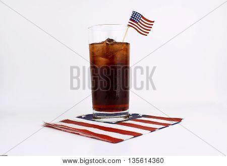 Tall glass of iced tea on a flag napkin with an American flag garnish