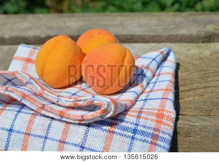Ripe apricots on wooden table on green background. Fresh apricots on wooden background