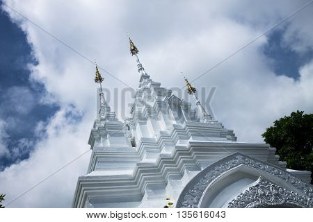 The traditionally decorated entrance way for thai temple situated in front of cloudy background. June 22-2016 Chiang Mai Thailand.