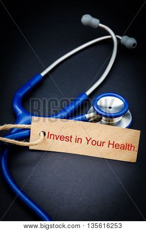 Invest in your health word in paper tag with stethoscope on black background - health concept. Medical conceptual