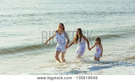 Family walking on the evening beach during sunset. Two children with mom.