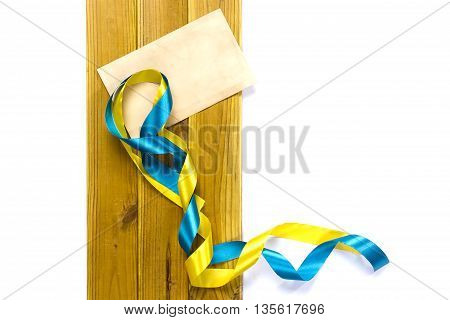 Yellow and blue satin ribbons on a wooden background