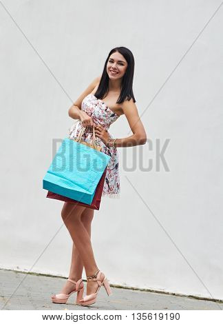 beautiful woman with many shopping bags on light background. about wall