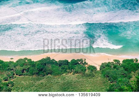 Paradise view above the sea. Idyllic aerial view of an empty tropical beach and vivid blue sea white foam waves in Bali, Indonesia.